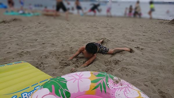 ビーチで砂まみれの子供